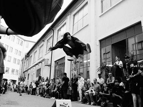 person greyscale photo of man jumping on street people