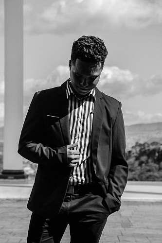 apparel greyscale photo of man wearing tuxedo clothing