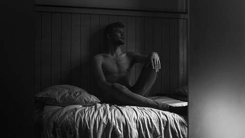 furniture greyscale photography of man sitting on bed bed