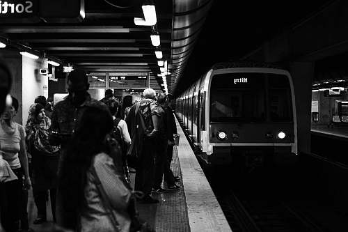 people group of people waiting for the train in grayscale photography subway