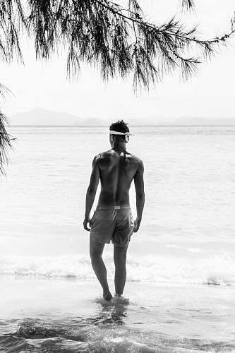 apparel half naked man in shorts with white bandana standing on shore during daytime back