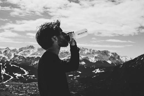person man drinking water on top of mountian human