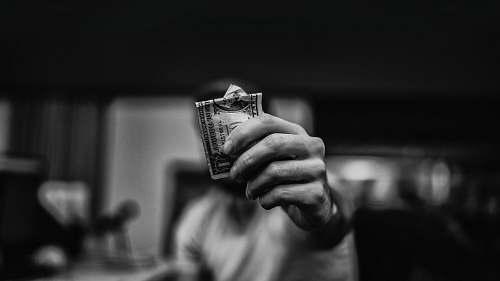 grey man holding 1 US dollar banknote bnw