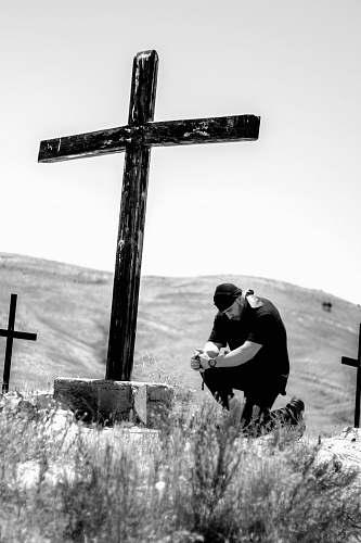 symbol man kneeling in front of wooden cross cross