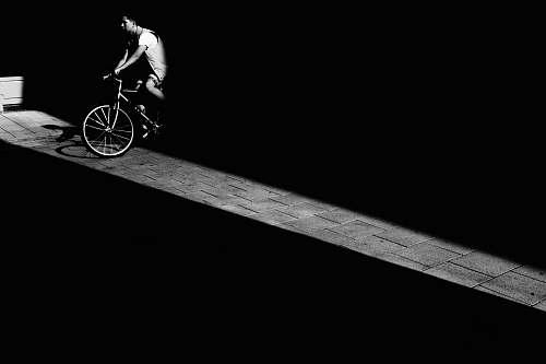 human man riding bicycle in dark area bicycle