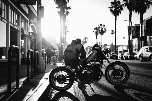 transportation man sitting on cruiser motorcycle on grayscale photograyphy motorcycle