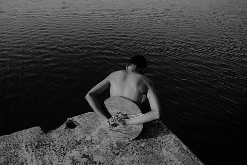 back man with round mirror on his back at the edge of rock island facing body of water danau buatan