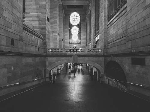 architecture people walking on hallway of concrete building with turned on chandelier lights in grayscale photography new york