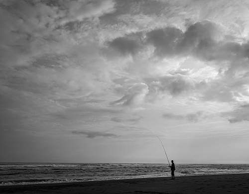 person person fishing on body of water grey