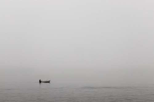 grey person sitting on white boat on ocean water nature