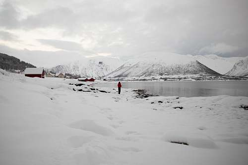 grey person standing beside lake near covered snow mountain during daytime mountain