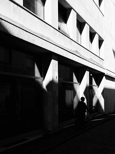 silhouette person walking near building street photography