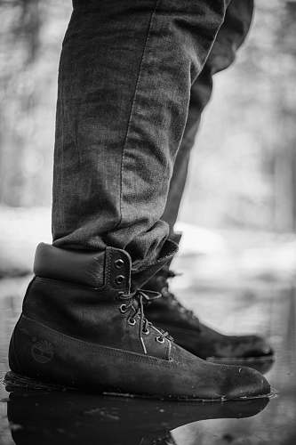 human person wearing black Timberland work boots stepping on water boot