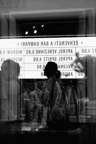 person reflection of people from glass panel walking and passing signage in grayscale photography human