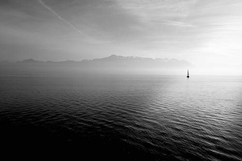 mountains sailboat on calm body of water under white sky at daytime desktop wallpapers