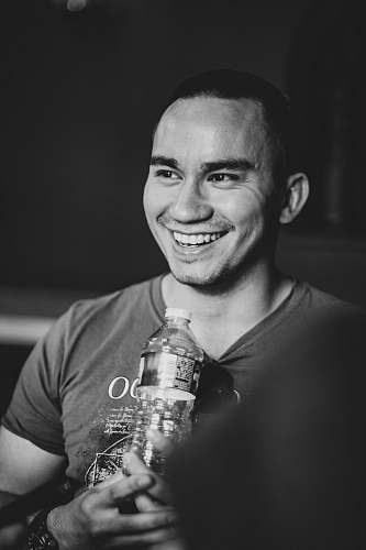 human smiling man holding clear bottled water people