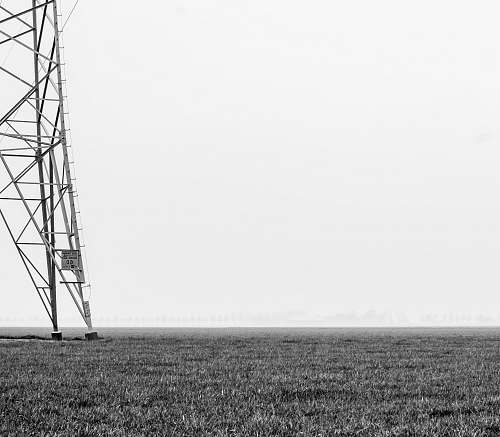 white steel transmission tower on grass plains field