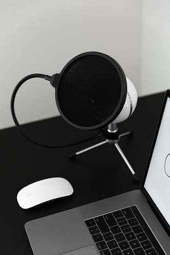 speaker turned-on MacBook Pro beside Magic Mouse electronics