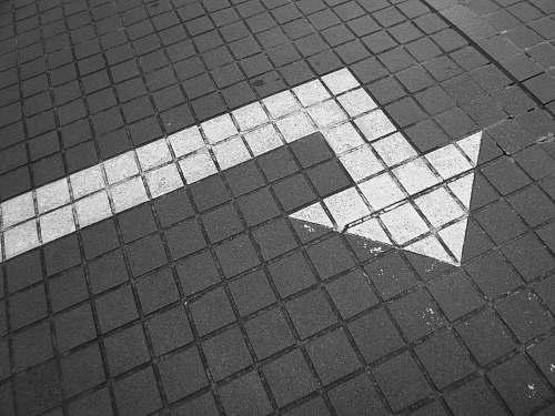 grey white arrow on bricked pavement flooring