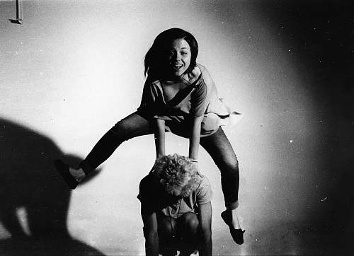 person woman jumping on other person's back in grayscale photography people