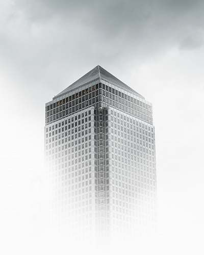 grey worm's-eye view photography of white and gray concrete building under cloudy sky architecture