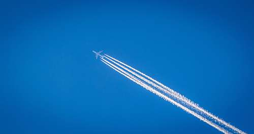 contrail white airplane flying under the blue sky sky