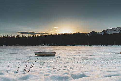 rowboat boat on frozen lake with silhouette of trees at distance transportation
