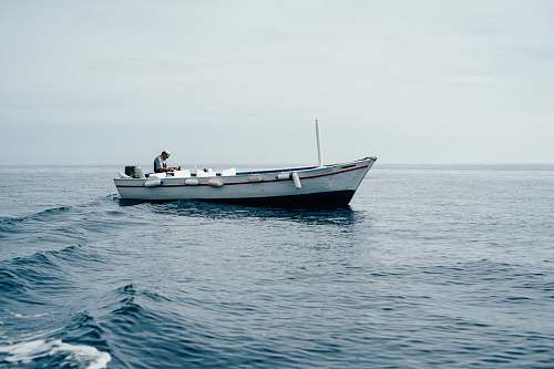 dinghy man sitting on boar in ocean ocean