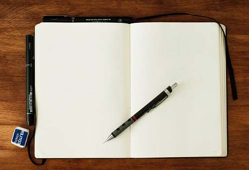 paper black and silver retractable pen on blank book blank