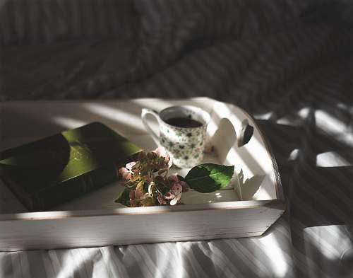 coffee teacup beside pink flowers on tray tea