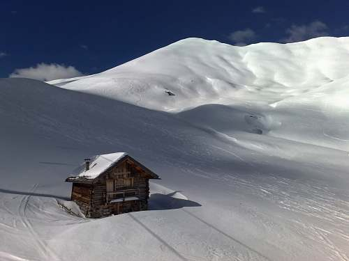 snow brown wooden house on the center of snow covered land winter