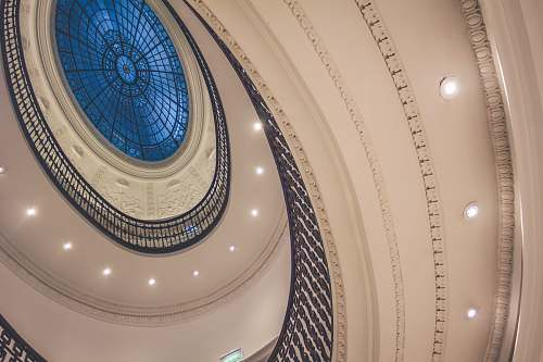 lights low-angle photo of white spiral building glass ceiling