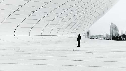 grey person standing in a middle of white plate field architecture