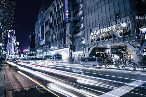 city time-lapse photography of asphalt road near buildings during nighttime dark