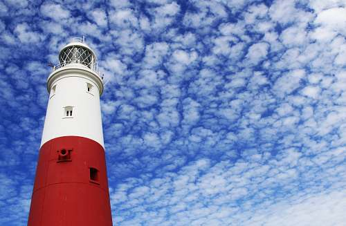 photo beacon white and red lighthouse under cloudy sky blue free for commercial use images