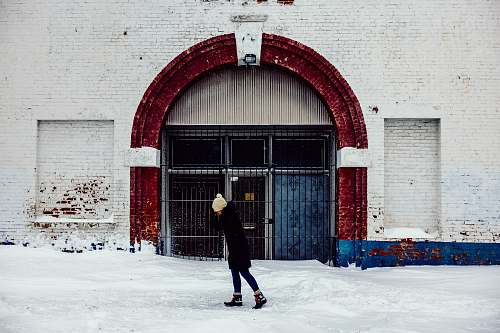 person woman standing in front of white concrete building snow