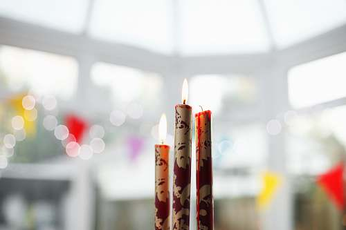 light three brown-and-red candles on top of table interior design