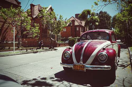 colombia red and white Volkswagen Beetle on road near brown house vehicle