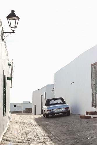 automobile silver car parked beside white building transportation
