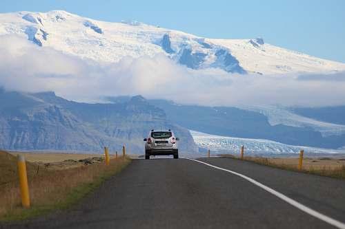 road white SUV passing through roadway mountain