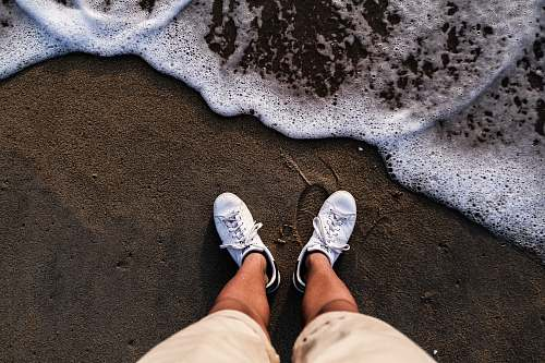 footwear person wearing white shoes standing on sea shore shoe