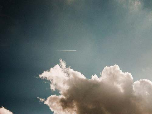 sky photo of contrail during cloudy daytime clouds
