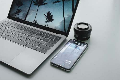 shade turned-on MacBook Pro beside black smartphone on gray surface tree