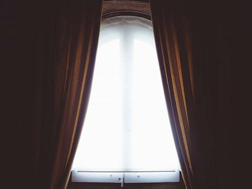 window clear glass window and brown curtain panel white