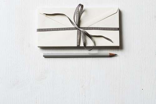 minimal white envelop and gray pencil on white panel white