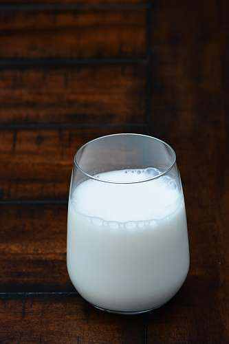 white clear drinking glass with white liquid milk