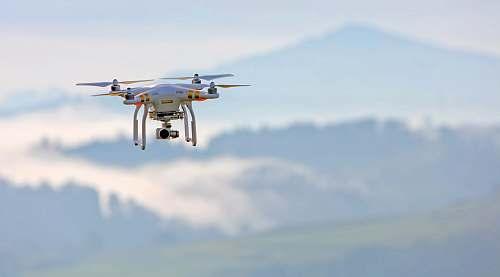 biplane shallow focus photo of white quadcopter transportation