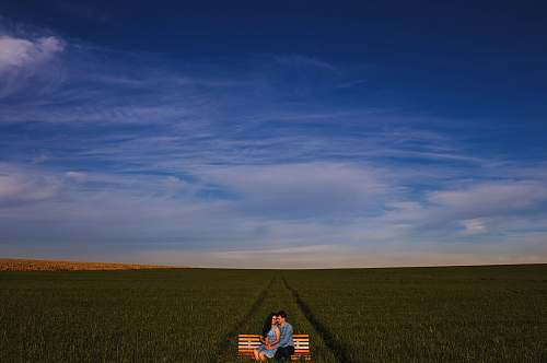 brazil photo of two man and woman sitting on bench on grass field love