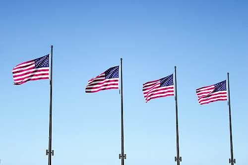 emblem four USA flags under blue sky pole