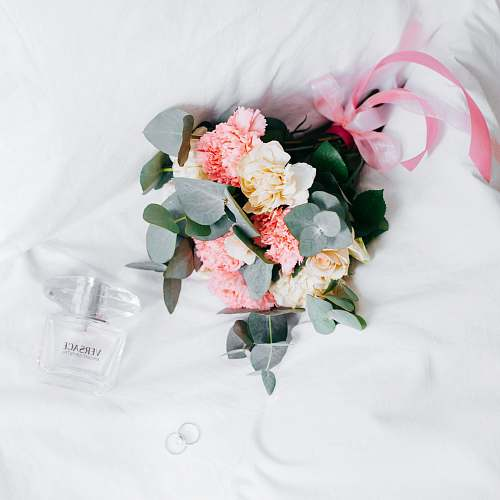 wedding bouquet of yellow-and-pink roses and chrysanthemums placed next to Versace spray bottleon white textile blossom